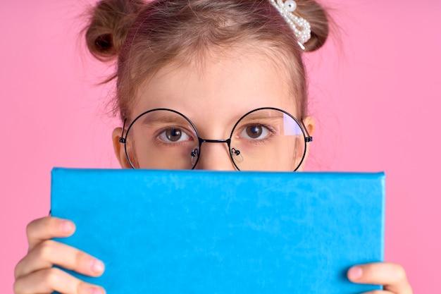 Ritratto di lei bella foxy bella attraente allegra ragazza scuola positiva che tiene nelle mani che si nascondono dietro la preparazione all'esame del libro aperto isolata sopra lo spazio rosa