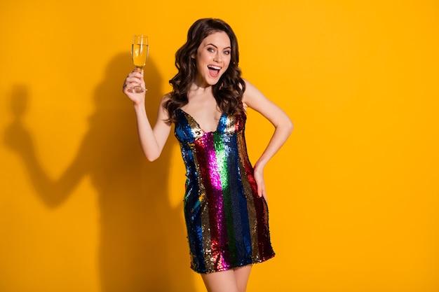 Ritratto di lei bella attraente bella felice slim fit allegra allegra signora dai capelli ondulati che beve vino frizzante divertirsi isolato brillante vivido brillantezza vibrante sfondo di colore giallo