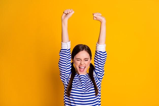 Ritratto di lei bella attraente bella bella riuscita allegra allegra ragazza dai capelli castani alzando le mani in alto celebrando isolato su sfondo di colore giallo brillante brillante brillantezza vibrante