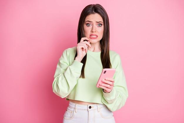 Ritratto di lei, bella, affascinante, attraente, piuttosto, nervosa, perplessa, insicura, confusa, dai capelli castani, usando la cella che legge le notizie del virus corona covid-19 isolate su sfondo rosa pastello