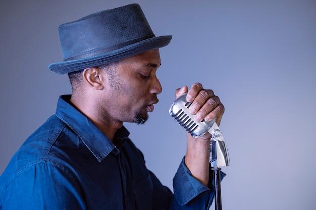 Ritratto di un uomo di colore attraente dei pantaloni a vita bassa che canta una canzone d'annata. canzoni culturali etniche d esecuzione isolate del maschio. giovane cantante afroamericano che tiene microfono d'avanguardia. componi e crea testi.