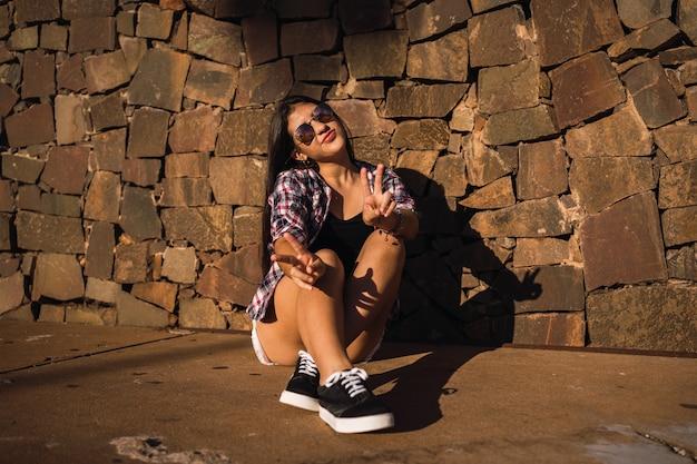 Ritratto di una ragazza hipster che fa il v o segno di pace.