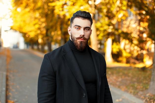 Ritratto di un uomo hipster con la barba in un elegante cappotto nero nella giornata di sole autunnale