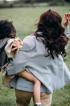 Ritratto di madre hipster con figlia in braccio nel campo. la famiglia si diverte insieme