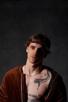 Il ritratto di una persona hipster con il corpo tatuato in giacca pone in uno sfondo scuro