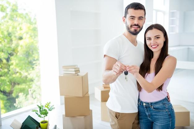 Ritratto di suo lui lei lei bella attraente bella allegro coniugi sposati che abbracciano tenendo in mano chiave affitto banca acquisto spazio sviluppo edilizio all'interno bianco luce piatta