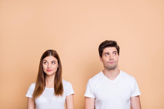 Ritratto di suo lui lei lei bella attraente bella curiosa coppia sconcertata indossando t-shirt bianca pensando creando soluzione apprendimento isolato su sfondo beige color pastello