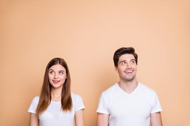 Ritratto del suo lui lei lei bella attraente bella curiosa allegra allegra intelligente intelligente intelligente coppia che indossa la maglietta bianca creando soluzione apprendimento isolato su sfondo beige color pastello