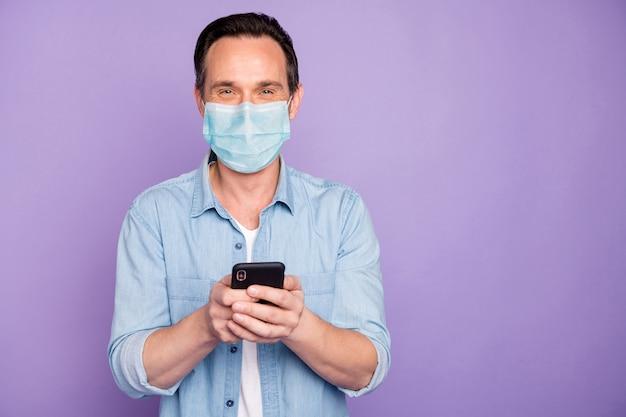 Ritratto del suo ragazzo maturo che utilizza il dispositivo navigando notizie cov mers pandemia influenzale wuhan cina infezione indossando maschera di garza di sicurezza isolato su sfondo viola lilla colore viola
