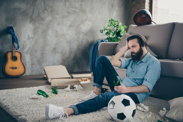 Ritratto di suo lui bello attraente triste deluso brunet ragazzo seduto sul pavimento che soffrono di postumi di una sbornia la mattina presto al loft industriale in stile moderno camera interna casa al chiuso