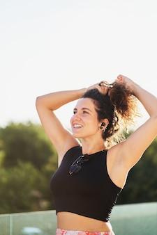 Ritratto di donna ispanica allegra che si aggiusta i capelli al tramonto