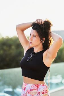Ritratto di donna ispanica che si aggiusta i capelli al tramonto