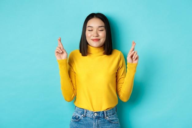 Ritratto di speranzosa ragazza asiatica che sogna il desiderio che si avvera, incrocia le dita per buona fortuna e sorride, implorando dio o supplicando, in piedi su sfondo blu
