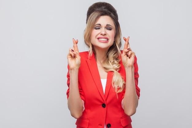 Ritratto di speranzosa bella donna d'affari con acconciatura e trucco in blazer rosso fantasia, in piedi, stringendo i denti, occhi chiusi e dita incrociate. girato in studio al coperto, isolato su sfondo grigio.