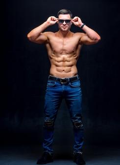 Un ritratto di un uomo forte bel ragazzo caldo senza camicia contro il buio