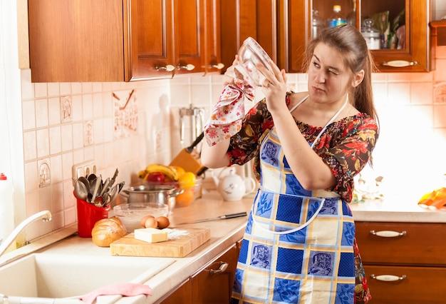 Ritratto di casalinga che controlla quanto è pulita la ciotola di vetro