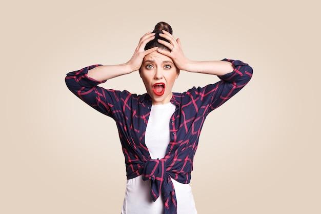Ritratto di isterica ragazza caucasica con i capelli a ciambella che guarda in preda alla disperazione e al panico, essendo in ritardo per un esame o un evento importante, non sapendo cosa fare, le mani sulla testa, la bocca spalancata. guardando la fotocamera.