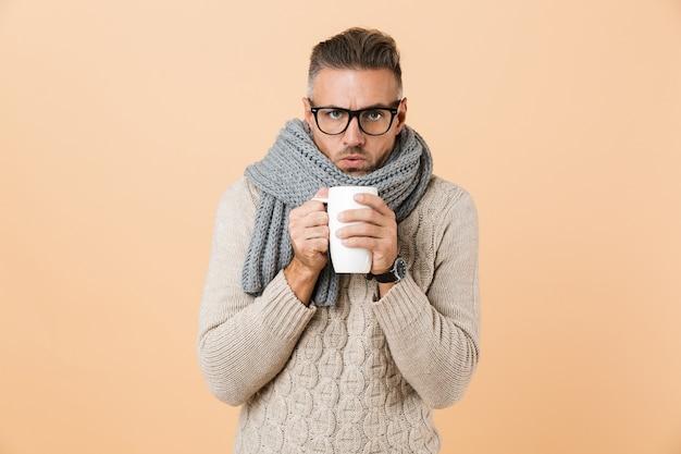 Ritratto se un uomo congelato vestito in maglione e sciarpa che tiene tazza di tè caldo isolato sopra il muro beige