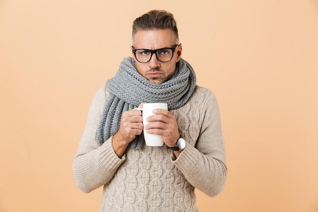 Ritratto se un uomo congelato in occhiali vestito con maglione e sciarpa che tiene tazza di tè caldo isolato sopra il muro beige