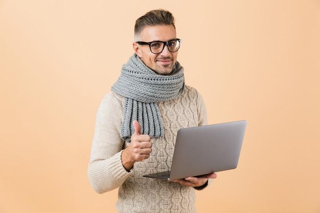 Ritratto se un uomo felice vestito in maglione e sciarpa in piedi isolato sul muro beige, tenendo il computer portatile, dando i pollici in su