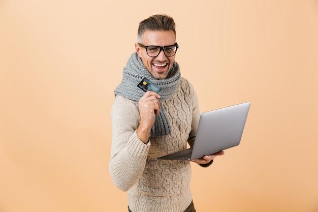Ritratto se un uomo felice vestito in maglione e sciarpa in piedi isolato sul muro beige, tenendo il computer portatile, mostrando la carta di credito in plastica