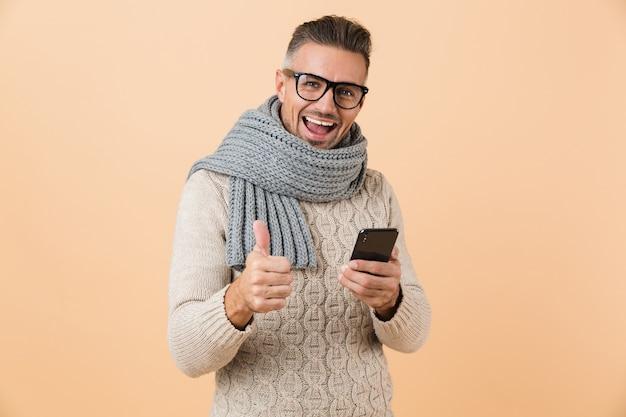 Ritratto se un uomo felice vestito in maglione e sciarpa in piedi isolato sopra il muro beige, tenendo il telefono cellulare, dando i pollici in su