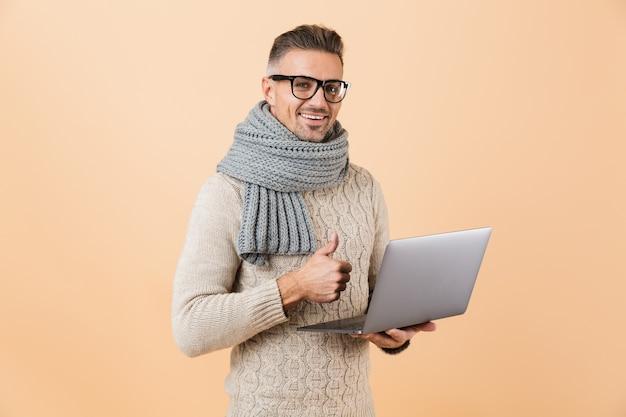 Ritratto se un uomo sorridente vestito in maglione e sciarpa in piedi isolato sul muro beige, tenendo il computer portatile, dando i pollici in su