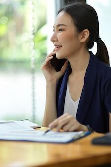 Immagine ritratto di un'imprenditrice asiatica che parla al telefono con un partner commerciale, effettua una telefonata, contatta clienti aziendali