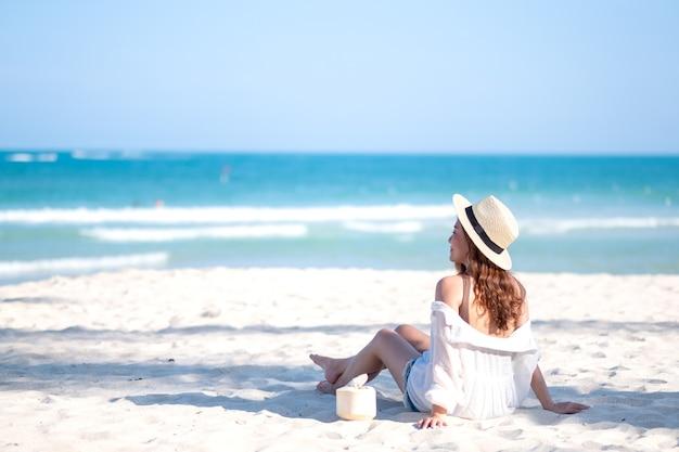 L'immagine del ritratto di bella donna asiatica gode di sedersi e bere il succo di cocco sulla spiaggia