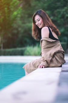 L'immagine del ritratto di una bella donna asiatica è piaciuta seduta a bordo piscina