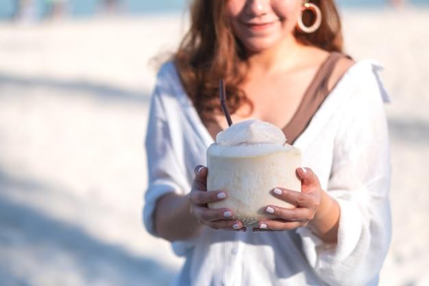 Immagine del ritratto di bella donna asiatica che tiene e che beve il succo di cocco sulla spiaggia