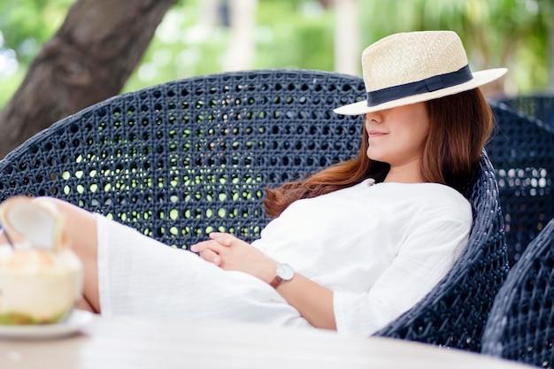 Immagine ritratto di una bella donna asiatica con cappello sdraiato e che dorme su una panchina in giardino con cocco sul tavolo