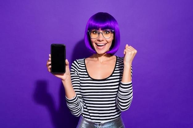 Ritratto del gadget della tenuta della gioventù adorabile impressionato che alza i pugni che grida wow omg isolate sopra fondo viola viola