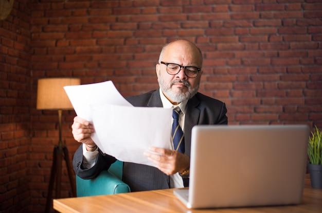 Ritratto di uomo d'affari senior asiatico indiano che lancia o legge documenti mentre è seduto alla scrivania con un laptop
