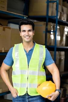 Ritratto del lavoratore asiatico indiano del magazzino con il supporto della maglia di sicurezza e la tenuta del casco giallo