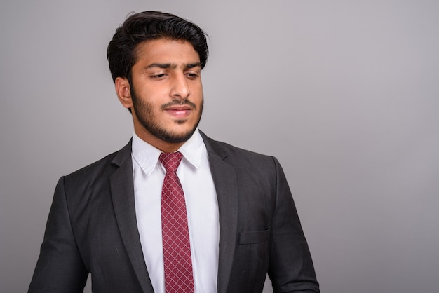 Ritratto di uomo d'affari indiano su sfondo grigio