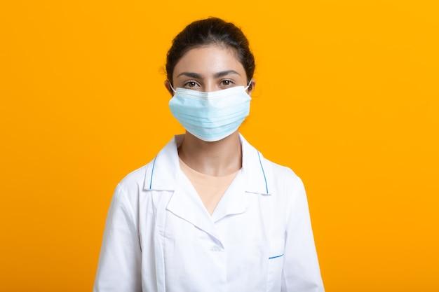 Ritratto di donna medico indiana che indossa abito medico bianco e maschera facciale isolata su sfondo giallo.