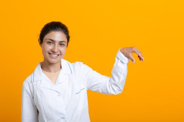Ritratto di donna medico indiana in abito medico bianco che tiene le dita modello vaccino covid-19 o altre cose mediche isolate su sfondo giallo.
