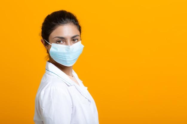 Ritratto di donna medico indiano in abito medico bianco isolato su sfondo giallo