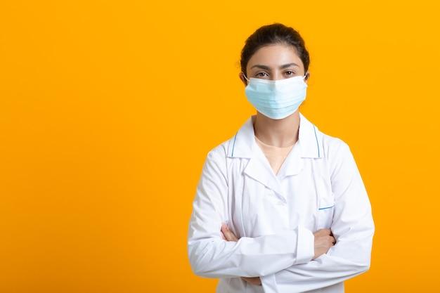 Ritratto di medico indiano donna in abito medico bianco isolato su sfondo giallo