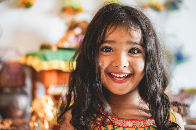 Ritratto della ragazza femminile indiana che indossa l'abito da sari - bambino asiatico meridionale divertendosi sorridente - infanzia, culture diverse e concetto di stile di vita
