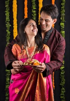 Ritratto di coppia sposata indiana in abbigliamento tradizionale a namaskara o preghiera o posa di benvenuto o tenendo puja thali