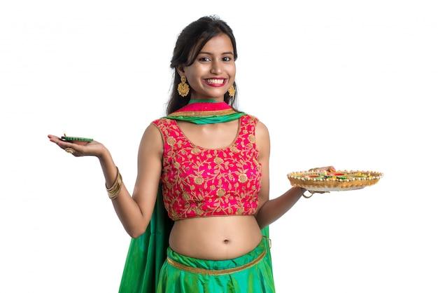 Ritratto di una ragazza tradizionale indiana che tiene diya e celebra diwali o deepavali
