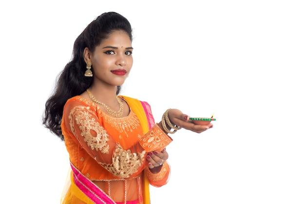 Ritratto della ragazza tradizionale indiana che tiene diya e che celebra il festival di diwali