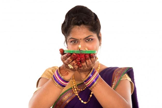 Ritratto di una ragazza indiana tradizionale in possesso di diya, diwali o deepavali foto con mani femminili in possesso di lampada a olio durante il festival di luce su sfondo bianco