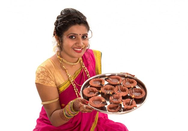 Ritratto di una ragazza indiana tradizionale in possesso di diya, diwali o deepavali foto con mani femminili in possesso di lampada a olio durante il festival di luce sulla superficie bianca