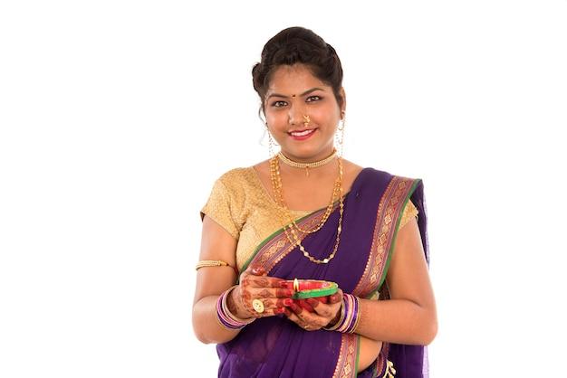 Ritratto di una ragazza tradizionale indiana che tiene diya, diwali o deepavali