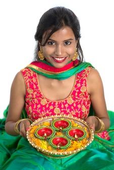 Ritratto di una ragazza indiana tradizionale in possesso di diya, ragazza che celebra diwali o deepavali con azienda lampada ad olio durante il festival di luce su sfondo bianco