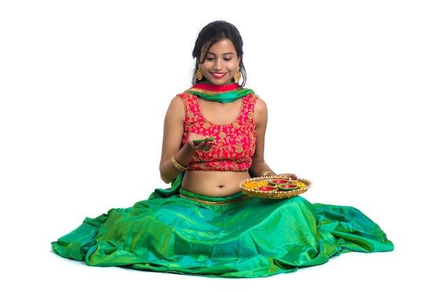 Ritratto di una ragazza indiana tradizionale con diya, ragazza che celebra diwali o deepavali con in mano una lampada a olio durante il festival di luce sulla superficie bianca