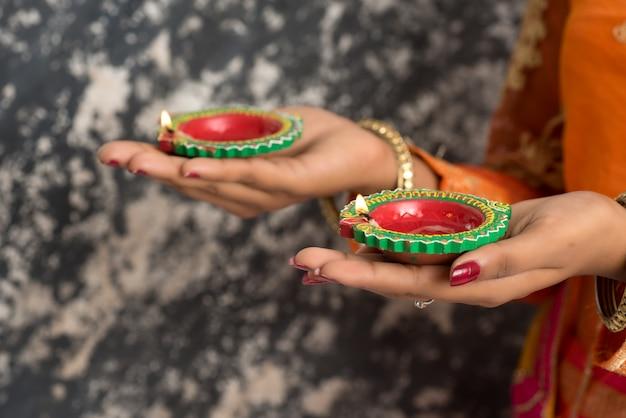 Ritratto di una ragazza tradizionale indiana che tiene diya, ragazza che celebra diwali o deepavali con la tenuta della lampada a olio durante il festival di luce.